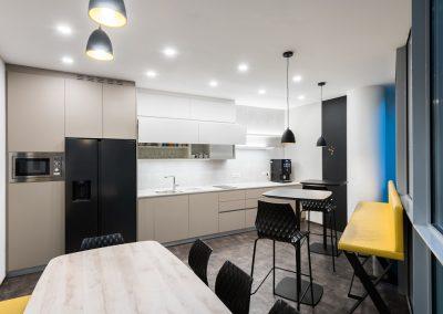 Kuhinja - nov prostor druženja; nenavadna oblika prostora ni ovira za funkcionalno rešitev.